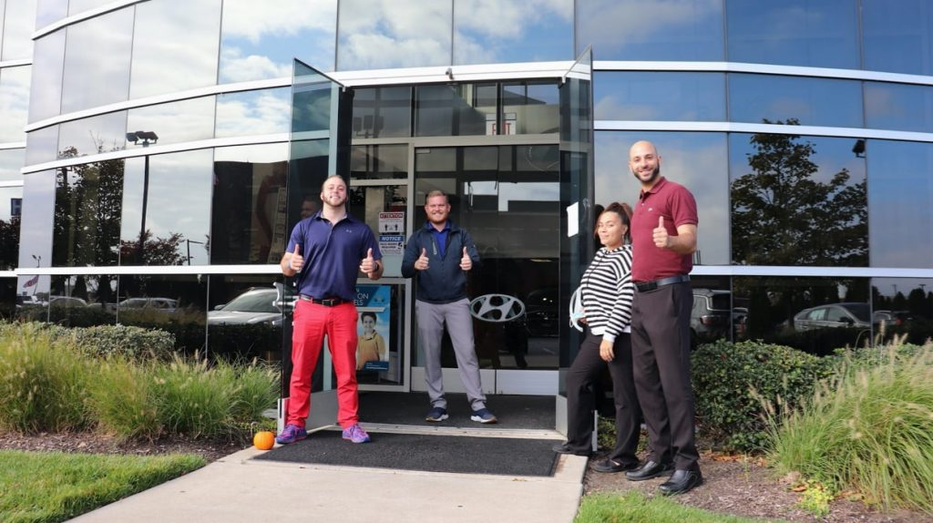 Three men and a woman in front of a Hyundai dealership